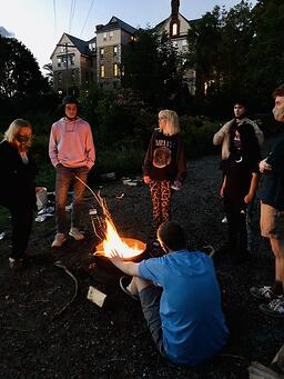 Teens making s'mores around a summer camp fire