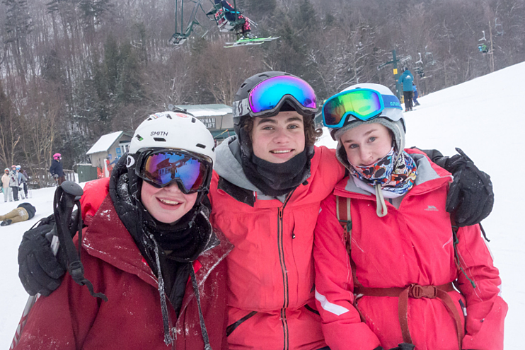 3 teens posing for a picture on the ski slopes