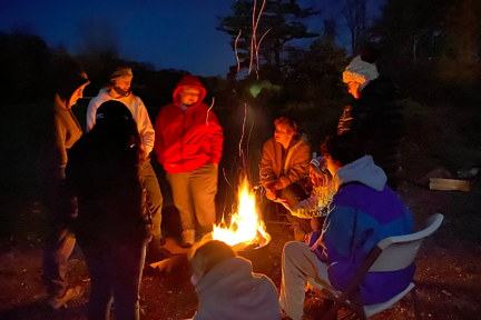 a group of teens gathered around a campfire in the winter