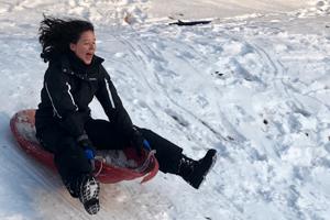 teen sledding down a hill