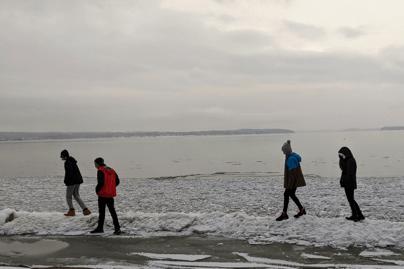 A group of teens taking a walk along Lake Champlain