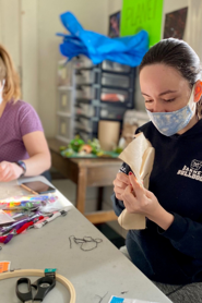 A teen in a mask doing arts and crafts