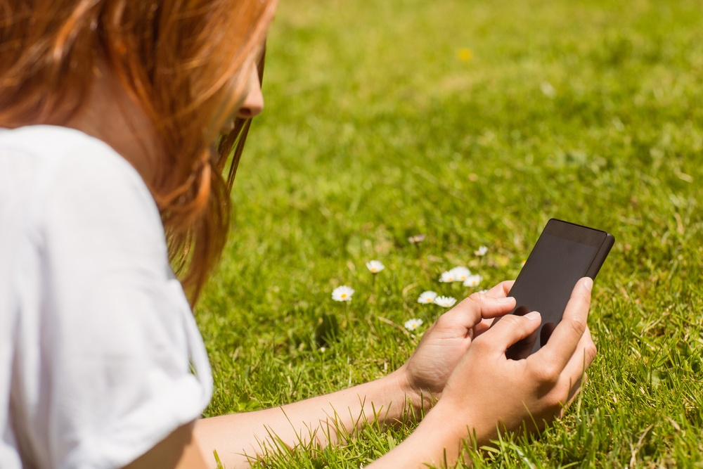 Pretty redhead text messaging on her phone lying on grass.jpeg