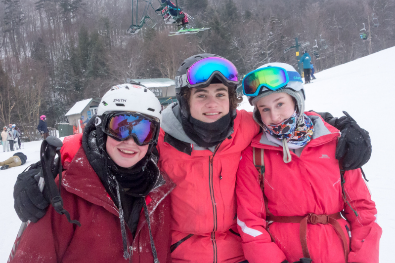 3 teens posing for a picture together on the ski slopes